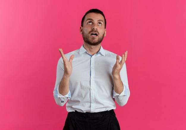 충격 된 잘 생긴 남자가 분홍색 벽에 격리 된 찾고 손을 올립니다