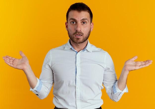 충격 된 잘 생긴 남자는 오렌지 벽에 고립 된 오픈 손으로 서