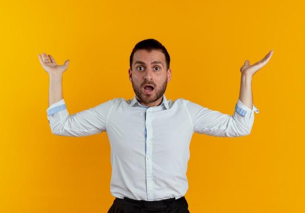 L'uomo bello scioccato sta con le mani alzate che sembrano isolate sulla parete arancione