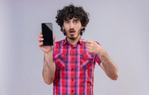 Un bell'uomo scioccato con i capelli ricci in camicia a quadri che punta al cellulare con il dito indice