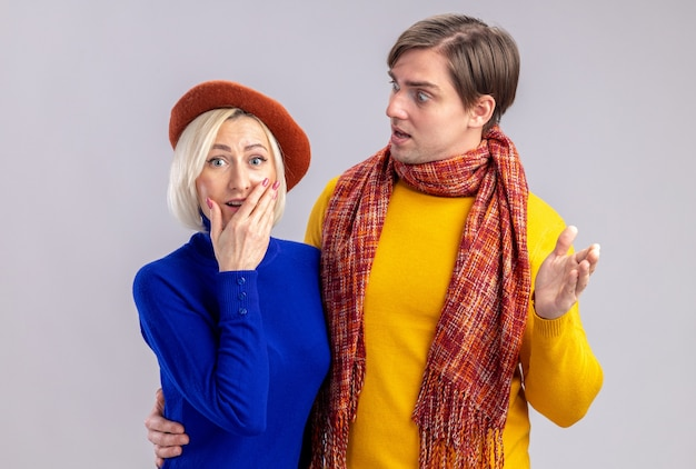 Shocked handsome slavic man with scarf around his neck looking at surprised pretty blonde woman with beret isolated on white wall with copy space
