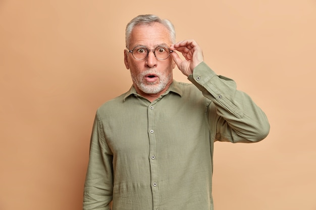 Shocked handsome stunned bearded elderly man has grey hair opens mouth widely keeps hand on spectacles cannot believe in shocking news wears formal shirt poses against brown studio wall