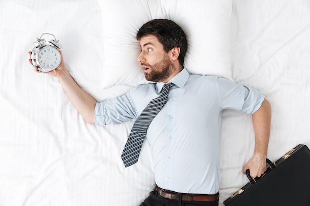 Шокированный красивый молодой бизнесмен утром в постели лежит с будильником