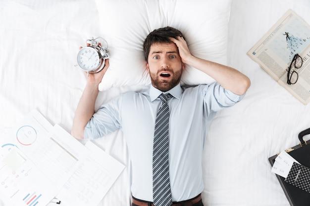 Шокированный красивый молодой бизнесмен утром в постели лежит спит с будильником