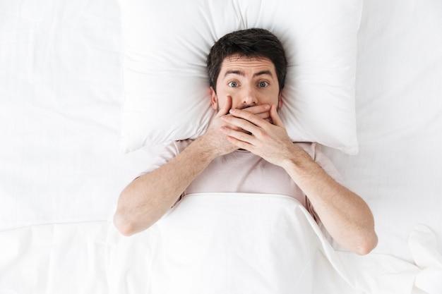 Шокированный красивый молодой человек утром под одеялом в постели лежит, прикрывая рот