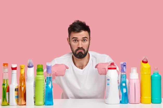 Un bel giovane scioccato indica se stesso con espressione indignata, chiede informazioni sui doveri domestici, indossa guanti di gomma