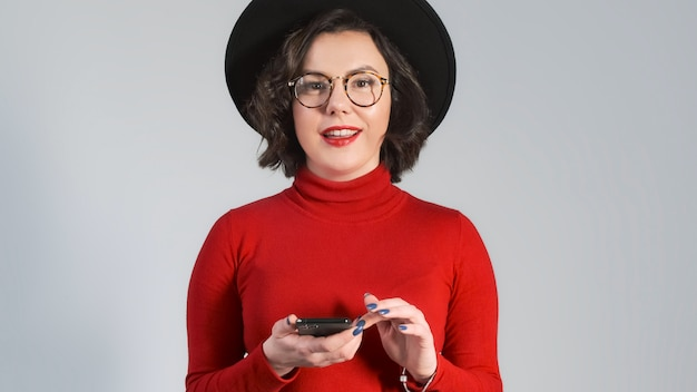 Shocked happy brunette woman woman in fashion hat using smartphone and is surprised. saying wow, looking at phone screen, lottery win.