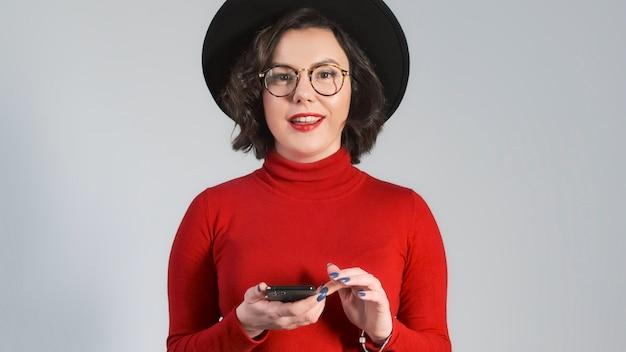 Сотрясенная счастливая женщина женщины брюнет в шляпе моды используя smartphone и удивлена. говорят вау, смотрят на экран телефона, выигрывают в лотерею.