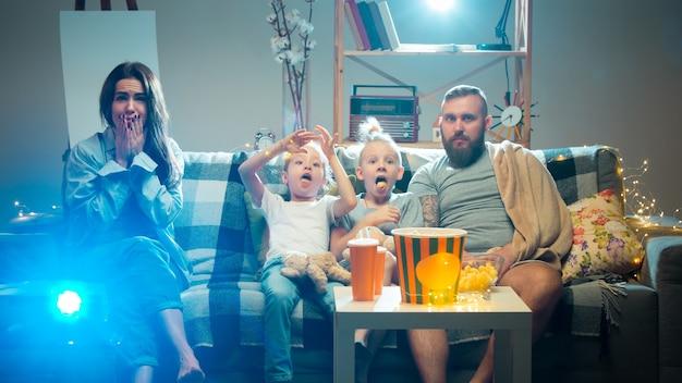 В шоке счастливая семья смотрит через проектор телевизионные фильмы с попкорном и напитками вечером дома