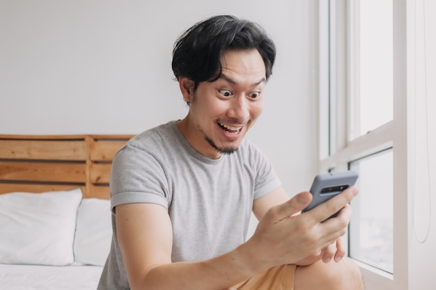 Shocked and happy man get good news from the smartphone