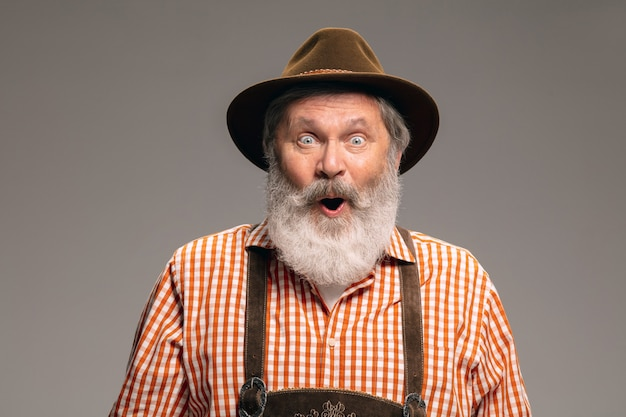 ショックを受けた。灰色のスタジオの背景に身振りで示す伝統的なオーストリアまたはバイエルンの衣装に身を包んだ幸せな年配の男性。コピースペース。お祝い、オクトーバーフェスト、お祭り、伝統のコンセプト。