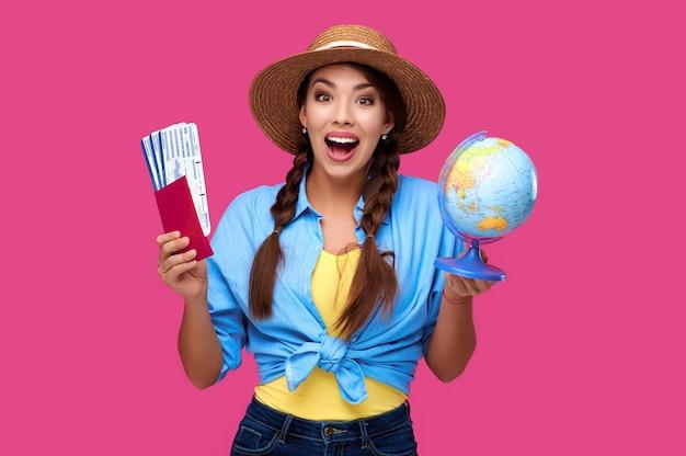 Сотрясенная счастливая женщина с паспортом и билетом, держащим глобус на изолированном фоне. концепция туризма