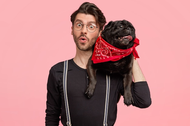 Shocked hipster guy with amazed facial expression, carries pedigree dog on neck, wears spectacles and black sweater, poses against pink wall, recieves unexpected news from vet. animals