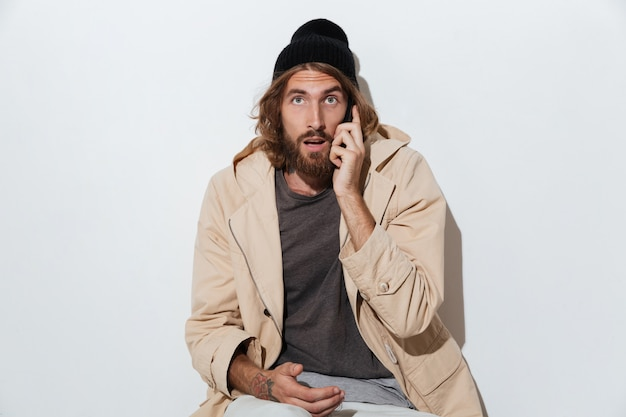 Shocked hipster man looking camera sitting isolated