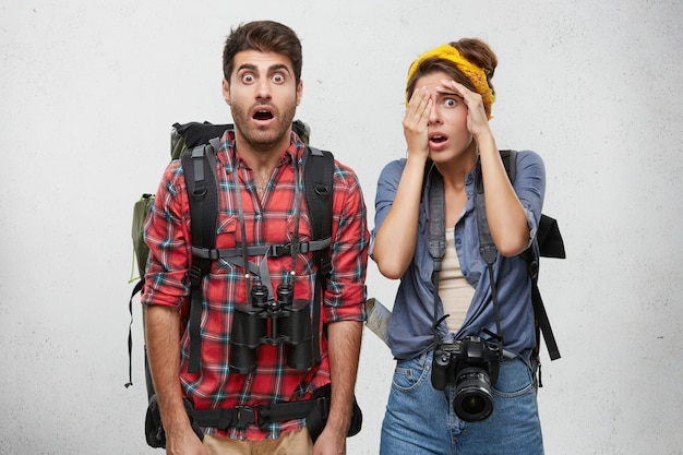 Shocked hitch hikers carrying backpacks, binoculars and camera, being tired after waiting for long time car