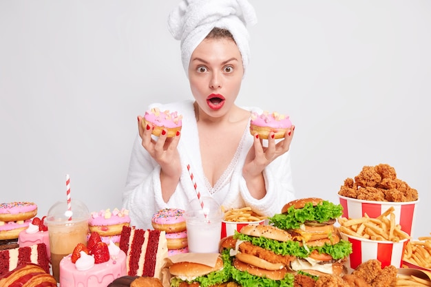 Shocked hungry woman eats high calorie fatty food holds two doughnuts looks wondered expression