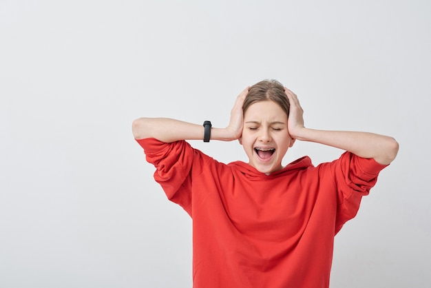 Shocked or hysteric teenage girl in red hoodie covering her ears while touching head and screaming against white background