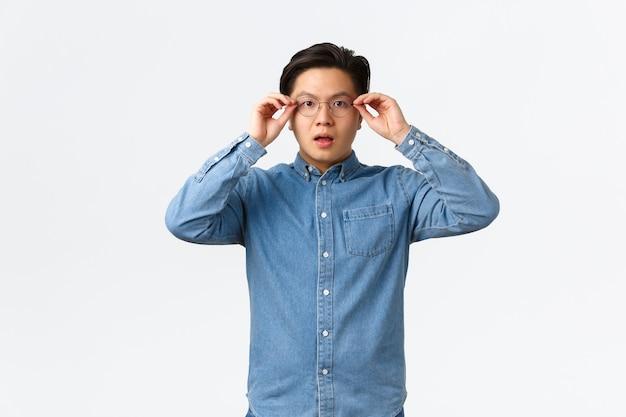 L'uomo asiatico scioccato e impressionato indossa gli occhiali per vedere qualcosa, sembra sorpreso e stupito, assiste a un grande evento, guarda un annuncio interessante, in piedi su sfondo bianco