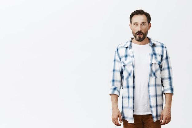 Shocked and impressed bearded mature man posing