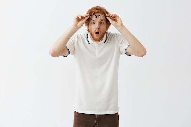 Ragazzo con la barba rossa scioccato e impressionato in posa contro il muro bianco con gli occhiali