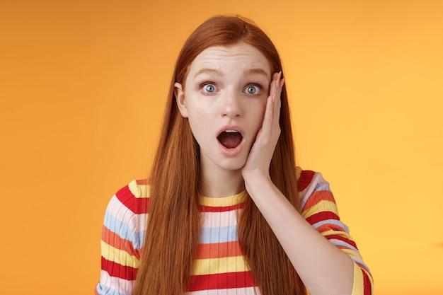 충격에 감명받은 생강 소녀 드롭 턱 헐떡이며 뺨을 뺨을 크게 벌리고 끔찍한 이야기를 동정하는 오렌지 배경 서있는 끔찍한 소식을 듣고 놀랐습니다. 공간 복사