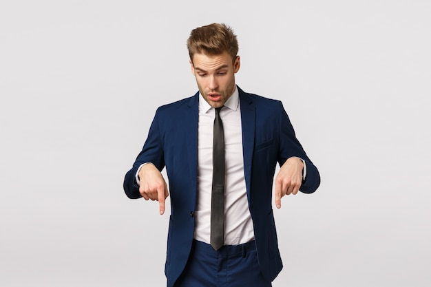 Shocked, impressed and curious blond bearded guy in classic suit, businessman pointing looking down speechless, standing astonished and impressed
