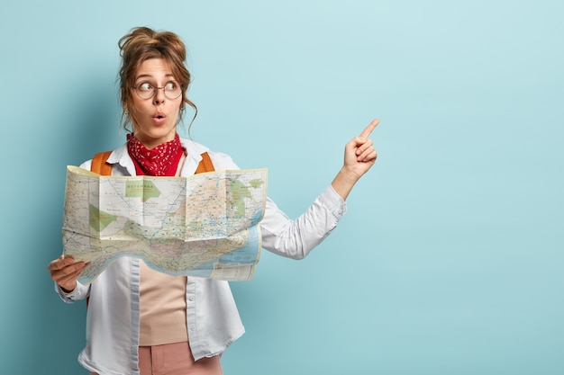 Shocked impressed female tourist points at copy space, holds travel map