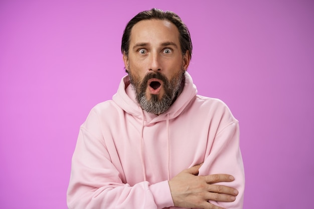 Shocked impressed gossiping caucasian bearded adult 40s man grey hair in pink hoodie gasping fascinated fold lips wow widen eyes astonished hearing interesting thrilling story, purple background.