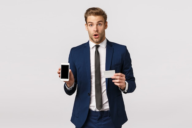 Shocked and impressed handsome businessman in stylish classic blue suit, holding credit card and smartphone, showing mobile display, say wow and stare astonished, promote financial app