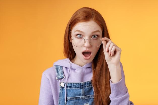 最後の親密な噂を聞いてショックを受けた感動した赤毛の同僚は、完全な不信のカメラを見つめている顎を落とします混乱したタッチグラスは、真実がオレンジ色の背景に驚いて立っているかどうかわからないようです。