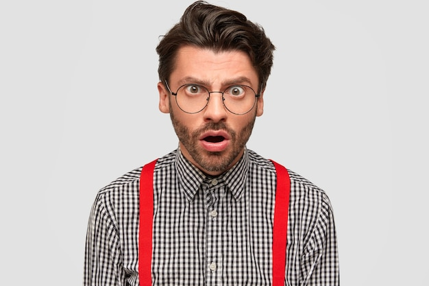 Shocked indignant male stares surprisingly, opens mouth from amazement, notices something unbelievable, dressed in checkered shirt and red braces, isolated over white wall