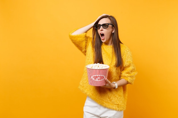 Shocked indignant young girl in 3d imax glasses putting hand on head, screaming watching movie film, hold bucket of popcorn isolated on yellow background. people sincere emotions in cinema, lifestyle.