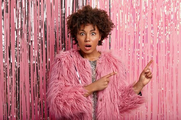 Giovane femmina sconvolta e intensa con taglio di capelli afro, indossa una pelliccia rosa, punta nell'angolo in alto a destra, tiene la mascella aperta, stupita di dimostrare qualcosa, stordita dall'udire la compagnia che fa rumore