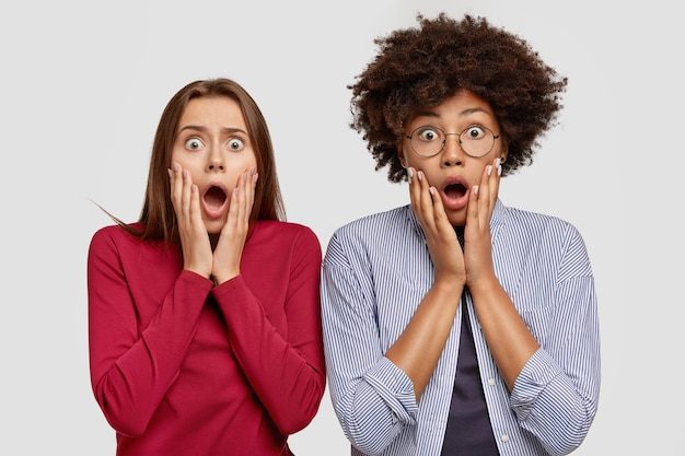 Giovani donne interrazziali scioccate reagiscono a notizie scioccanti, tengono la bocca aperta, stanno una accanto all'altra