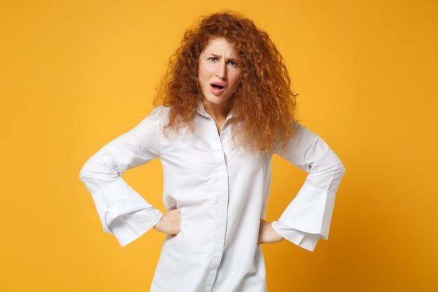 Scioccato irritato giovane donna rossa ragazza in camicia bianca casual in posa isolata sul muro giallo arancione