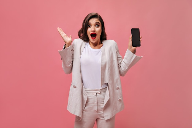 Shocked lady in cotton suit demonstrates phone on pink background.  surprised woman with bright lips in white clothes holds phone in her hands.