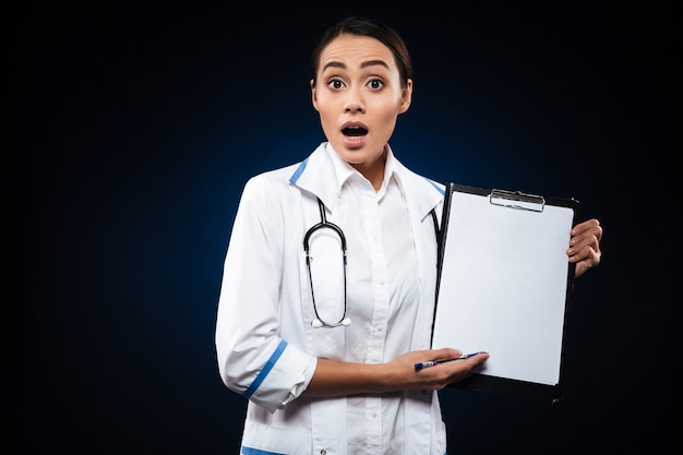 Shocked lady doctor in white medical gown showing blank clipboard isolated