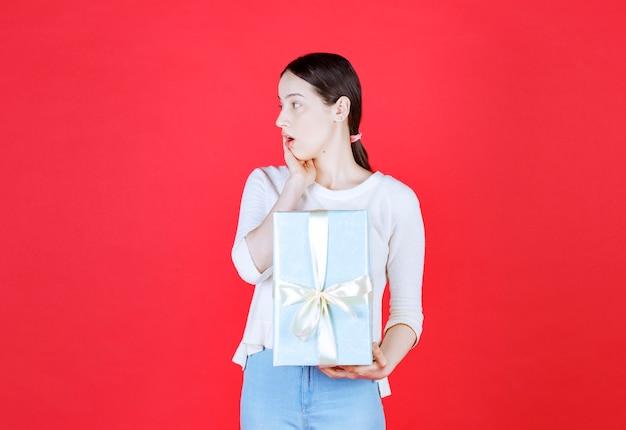 Signora scioccata che tiene in mano una confezione regalo e distoglie lo sguardo