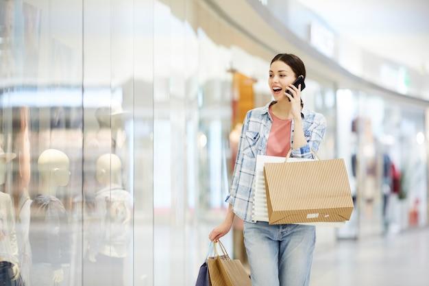 Шокированная леди шопоголик разговаривает по телефону