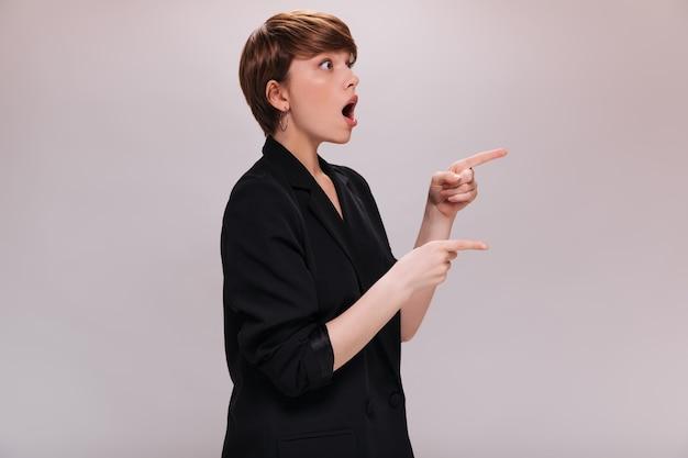 La signora scioccata in tuta indica il luogo per il testo su sfondo bianco. donna dai capelli corti sorpresa in giacca nera posa su sfondo isolato