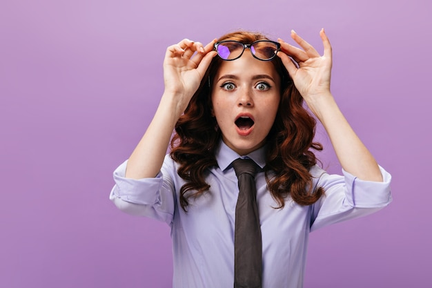 Shocked lady takes off her eyeglasses on purple wall