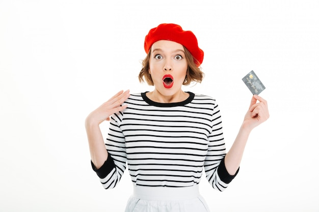 Shocked lady with opened mouth holding credit card and looking camera isolated