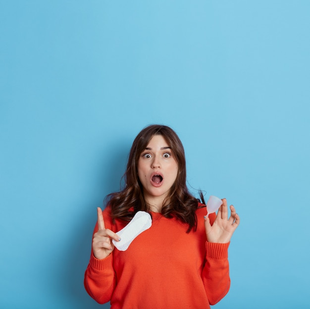 Shocked lady with widely opened mouth holding menstrual cup and cotton pad