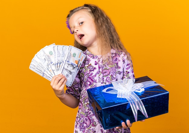 Shocked little blonde girl holding gift box and money isolated on orange wall with copy space