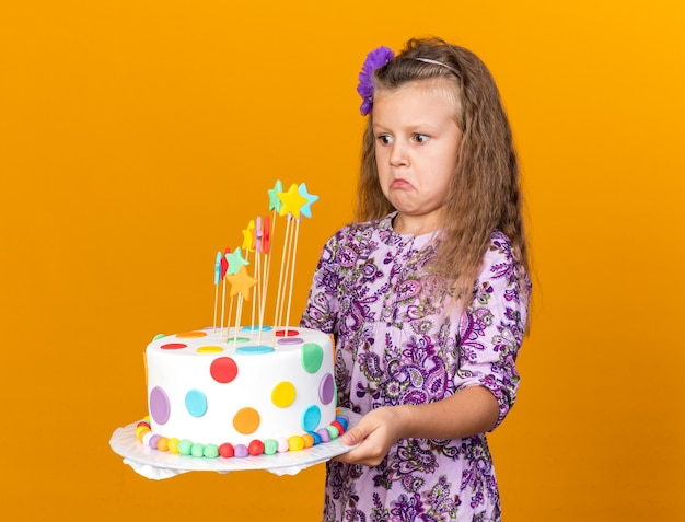 Shocked little blonde girl holding and looking at birthday cake isolated on orange wall with copy space
