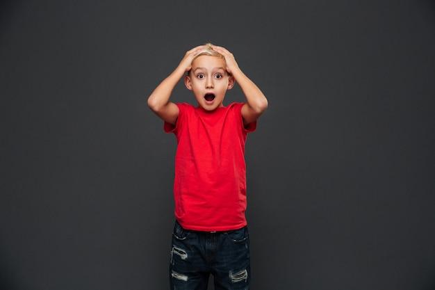 Шокирован маленький ребенок мальчик стоял изолированные