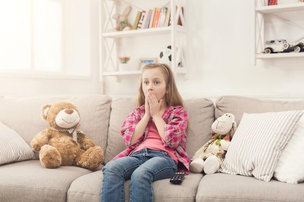Tv를 보고 충격을 받은 캐주얼 소녀. 겁에 질린 여자 아이는 소파에 앉아 혼자 집에 있고 장난감 친구 테디베어와 양과 함께 금지된 무서운 영화를 보고 공간을 복사합니다.