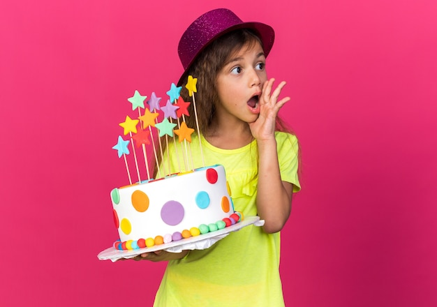 Shocked little caucasian girl with purple party hat putting hand on face and holding birthday cake looking at side isolated on pink wall with copy space