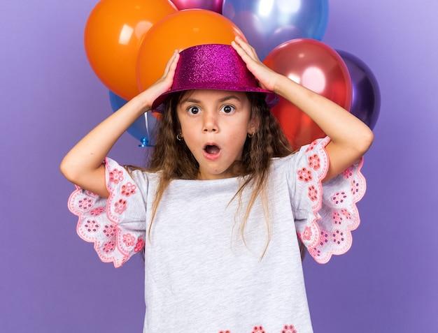 Piccola ragazza caucasica scioccata con il cappello viola del partito che mette le mani sul cappello in piedi davanti a palloncini di elio isolati sulla parete viola con lo spazio della copia
