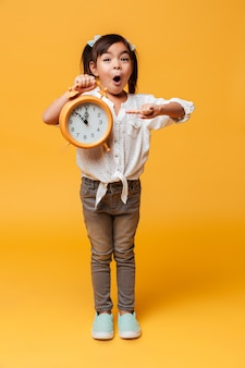 Shocked little girl child holding clock alarm.